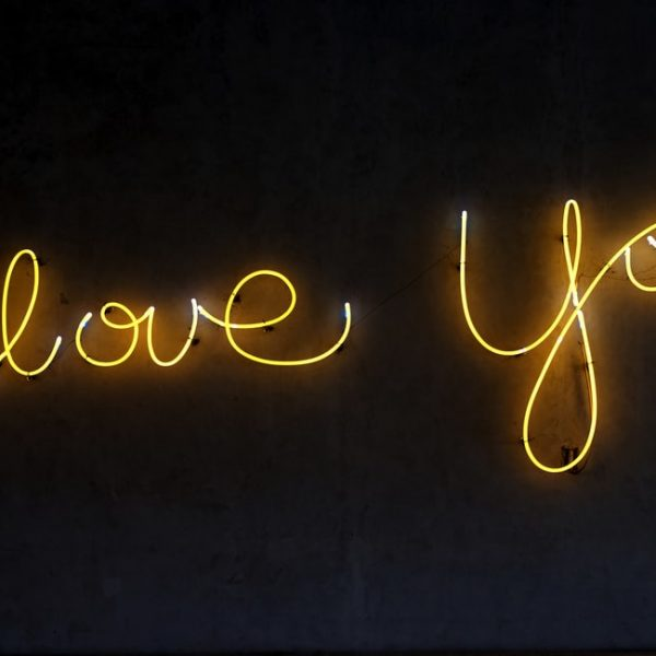 celebrating the ideal freelance client with neon lights that read i love you on a black background