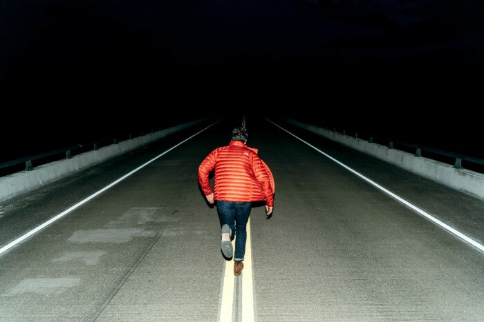 Man running in the middle of the road at night