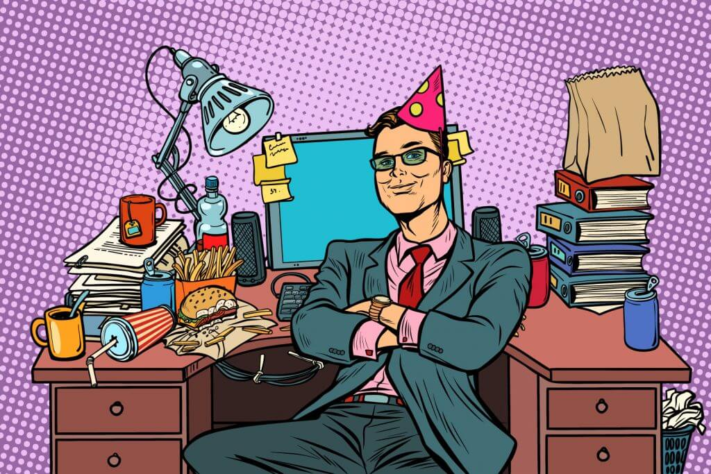 Business man with a party hat on at a messy desk
