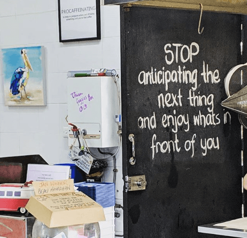 A quote is written on chalk in a cafe that reads stop anticipating the next thing and enjoy what's in front of you. It illustrates the curse of business perfectionism
