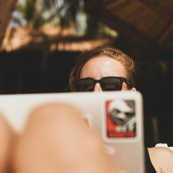 A lady is sitting behind a laptop with her knees up to signify remote work conditions. She has sunglasses on and is feeling casual.