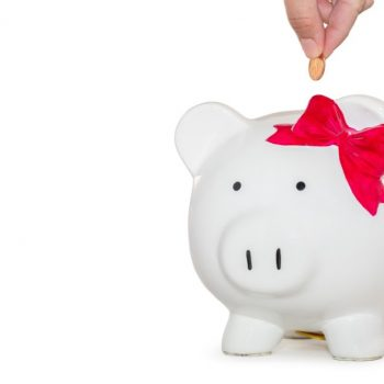 Illustrating the idea of saving on a marketing budget with a white ceramic piggy back wearing a bow. There is a hand dropping coins into the piggy bank.