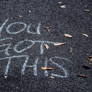 a bitumen road has 'you got this' scrawled on it in chalk. Used to demonstrate the power of confidence in coaching and mentoring.
