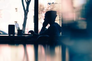 A side profile of a shadowed figure to demonstrate hiring freelancers. This person has a beanie on and looking intently at their laptop in a cafe window.