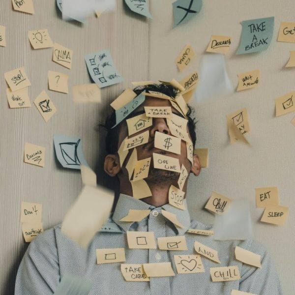 A person in a business shirt with collar has it buttoned to the neck. They are smothered in post-it notes, which obscure their face. This is the epitome of workplace stress, especially in agile team environments