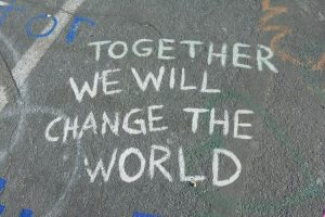 a bit of chalk is written on the sidewalk- it reads 'together we will change the world' - which is a common sentiment during this time of cultural transformation