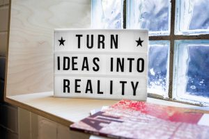 a lightbox says turn ideas into reality. It sits on a sideboard. A foundation marketing plan is all about turning your ideas into reality.