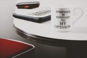 A coffee mug reads everyone is entitled to my opinion. It is on a table. It demonstrates unsolicited advice giving.