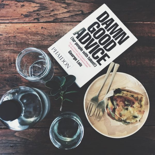 On a wodden table, a flat lay of toast, two glasses of water, a bottle and a book entitled damn good advice lie. It's to denote the whole advice culture with cafe side that business and life coach people are enamoured with.