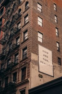 """On the side of a brick building in NYC, there is a big poster that reads """"how are you really?"""" In this context, it's meant to allude to mental health in the workplace."""