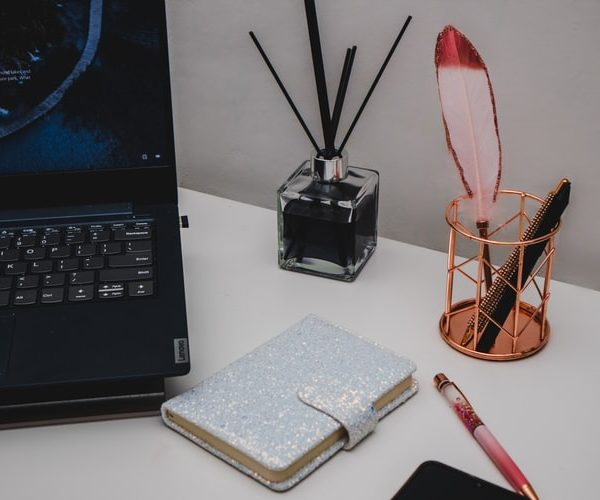 Looking at the desk of a conceptual copywriter there is a laptop, diary with clasp, an oil diffuser and a bottle of pens ready to go.